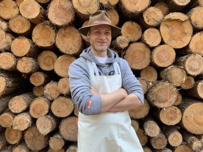 Unser Fleischermeister Kai steht vor einem Holzstapel